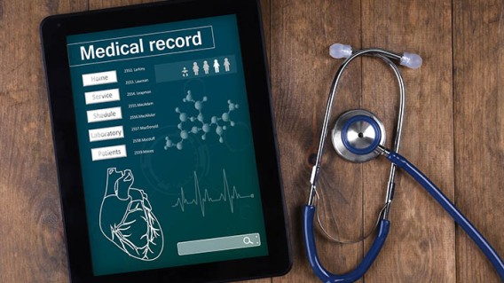 Medical record on tablet screen with stethoscope on wooden backg